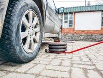 Pneumatyczna dźwigarka kłama na dachówkowej podłodze obok zakurzonego samochodu w samochodowym remontowym sklepie obrazy stock