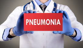 Pneumonia. Doctor`s hands in blue gloves shows the word pneumonia. Medical concept Stock Photography