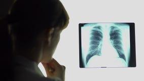 A pneumonia, terapeuta que analisa os pulmões radiografa a imagem, fazendo conclusões, cuidados médicos video estoque
