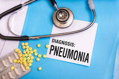 Pneumonia word written on medical blue folder. With patient files, pills and stethoscope on background stock image