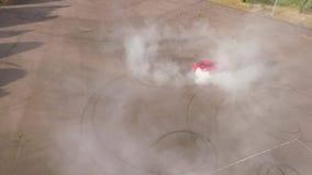 Pneus brûlants de voiture rouge banque de vidéos