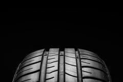 Pneus de carro econômicos em combustível do verão no fundo preto Imagem de Stock Royalty Free