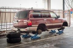 Pneus de SUV grande que está sendo mudado na loja do serviço do carro Pneumáticos do inverno fotografia de stock