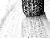 Pneus de voiture dans la neige sur la bande de roulement luisante glaciale de route images stock