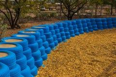 Pneus en caoutchouc bleus utilisés comme pare-chocs pour de petits enfants au désert P Photos libres de droits