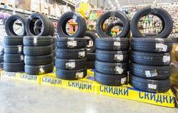 Pneus tous neufs empilés en vente dans l'hypermarché à chaînes Image libre de droits