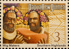 PNG postage stamp, wig makers. Papua New Guinea unused postage stamp showing  wig makers, Southern Highlands. Circa 1975. Isolated on black background Royalty Free Stock Image