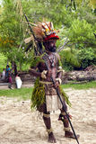 PNG warrior in traditional costume, wearing birds colorful feathers , holding spear during village celebrations Royalty Free Stock Image