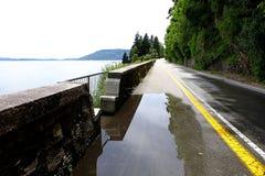 Poça após o chuveiro de chuva pesada na estrada Foto de Stock Royalty Free