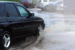 Poça da chuva do carro que espirra a água Fotografia de Stock Royalty Free