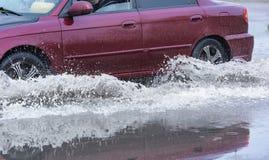 Poça da chuva do carro que espirra a água Imagem de Stock Royalty Free