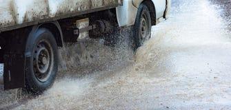 Poça da chuva do carro que espirra a água Imagens de Stock Royalty Free