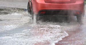 Poça da chuva do carro que espirra a água Foto de Stock