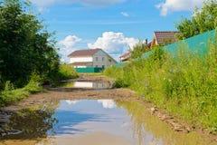 Poças em uma estrada de terra em uma vila Foto de Stock Royalty Free