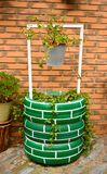 poço de água urbano que decora um jardim urbano com os pneus pintados, uma cubeta cinzenta com plantas em um fundo do tijolo foto de stock royalty free