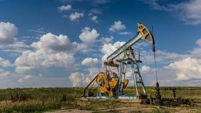 Poço de petróleo e gás de funcionamento perfilado no céu nebuloso imagens de stock royalty free