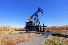 Poço de petróleo no campo de milho imagens de stock