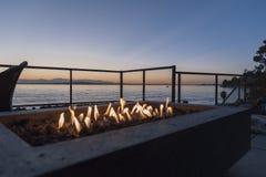 Poço do fogo pelo mar no por do sol Fotos de Stock Royalty Free