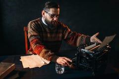 Poète barbu en verres dactylographiant sur la machine à écrire Images libres de droits