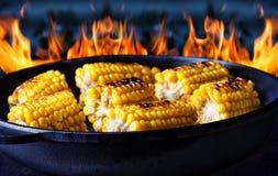 Poêle avec du maïs frit sur le fond du feu Images libres de droits