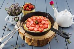 Poêle de fonte avec le tarte fait maison de fraise sur le deco en bois de dalle Image libre de droits
