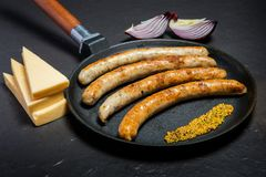 Poêle de plan rapproché avec les saucisses minces frites et la moutarde granulaire photos libres de droits