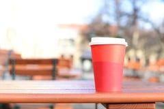 Połówka gorąca kawa w czerwonej papierowej filiżance na drewnianym stole w plenerowym Zdjęcie Stock