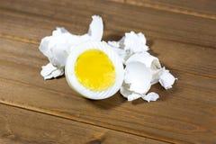 Połówka hardboiled jajka z skorupami kłaść na kuchennym stole fotografia royalty free