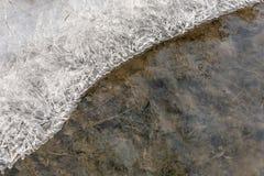 Połówka marznąca woda z lodowymi kryształami na powierzchni jako zimy tło obrazy royalty free