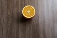 Połówka pomarańcze na drewnianym stole Zdjęcia Stock