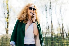 Połówka profilowy portret atrakcyjna kobieta jest ubranym elegancki odzieżowego opowiada na mądrze telefonie z kędzierzawym włosy obraz royalty free