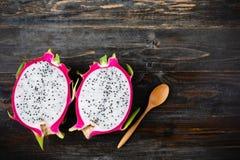 Połówka smok owoc z łyżką na drewnianym stole Zdjęcia Stock