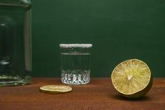 Połówka wapno Z Zamazanym wapno plasterkiem, Srebnym Tequila strzałem Rimmed Z solą I butelką Na Drewnianym wieśniaka stole, Ziel obrazy royalty free