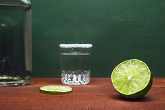Połówka wapno z Zamazanym wapno plasterkiem, Srebnym Tequila strzałem Rimmed z solą i butelką na Drewnianym wieśniaka stole z zie obrazy stock