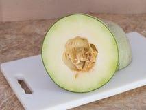 Połówka Zielony japoński melon na białym bloku w kuchni Zdjęcia Royalty Free