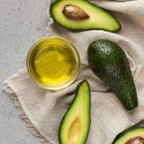 Połówki, cali avocadoes i puchar olej na pielusze zdjęcie stock