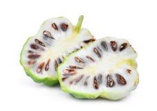 Połówki cięcie noni owoc na bielu Zdjęcie Stock