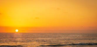 Położenia słońce Barwi ocean pomarańcze i niebo zdjęcie stock