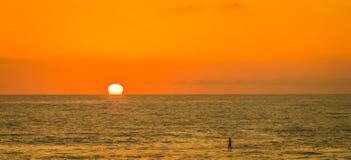 Położenia słońce Barwi ocean pomarańcze i niebo fotografia stock