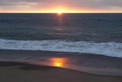 Położenia słońce na oceanu brzeg Zdjęcie Royalty Free