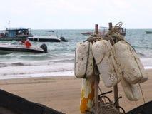 Połowów elementy umieszczali na plaży z morzem w tle Obraz Stock