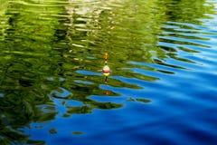 Połowu pławik na wodnej powierzchni jezioro podczas gdy łowiący zdjęcia stock