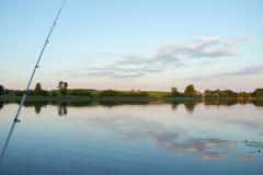 połowu prącie przeciw jaskrawemu jezioru z płocha lasem i most przy pogodnym letnim dniem zdjęcia stock