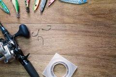 Połowu prącie, wabije, haczyki, rolka i sznurek na rocznika grunge drewnianym tle, zdjęcie stock