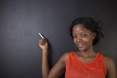 Południe - afrykanin lub amerykanin afrykańskiego pochodzenia kobieta nauczyciel lub studencka chwytów punktów kreda na blackboar Zdjęcie Stock