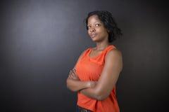 Południe - afrykanin lub amerykanin afrykańskiego pochodzenia kobieta nauczyciel na kredowym czerni deski tle Zdjęcia Stock