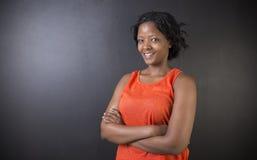 Południe - afrykanin lub amerykanin afrykańskiego pochodzenia kobieta nauczyciel na kredowym czerni deski tle Obrazy Stock