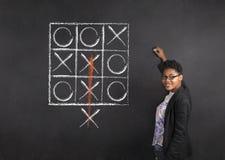 Południe - afrykanin lub amerykanin afrykańskiego pochodzenia kobieta nauczyciel pisze tic tac palec u nogi na kredowym czerni de Zdjęcia Royalty Free