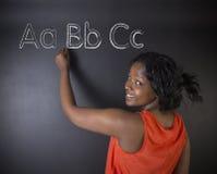 Południe - afrykanin lub amerykanin afrykańskiego pochodzenia kobieta uczeń lub nauczyciel uczymy się abecadło piszemy writing Obraz Royalty Free