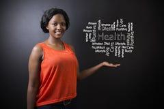 Południe - afrykanin lub amerykanin afrykańskiego pochodzenia kobieta uczeń przeciw blackboard zdrowie diagramowi lub nauczyciel zdjęcie royalty free